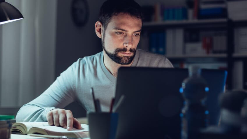 man looking at his notebook and laptop in the dark