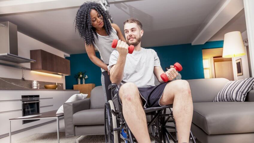 man in wheelchair working out with woman behind him