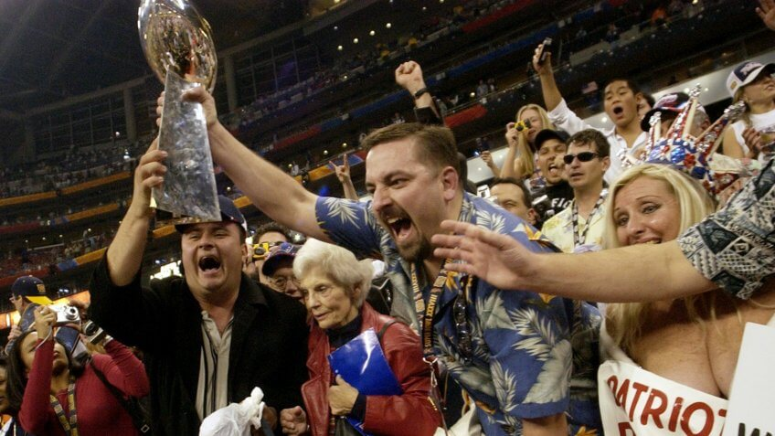 fans holding super bowl trophy