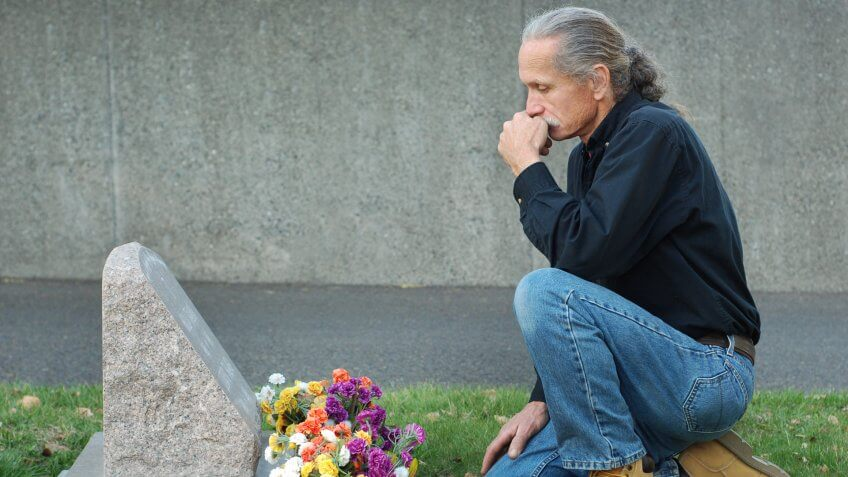 man mourning over a tombstone