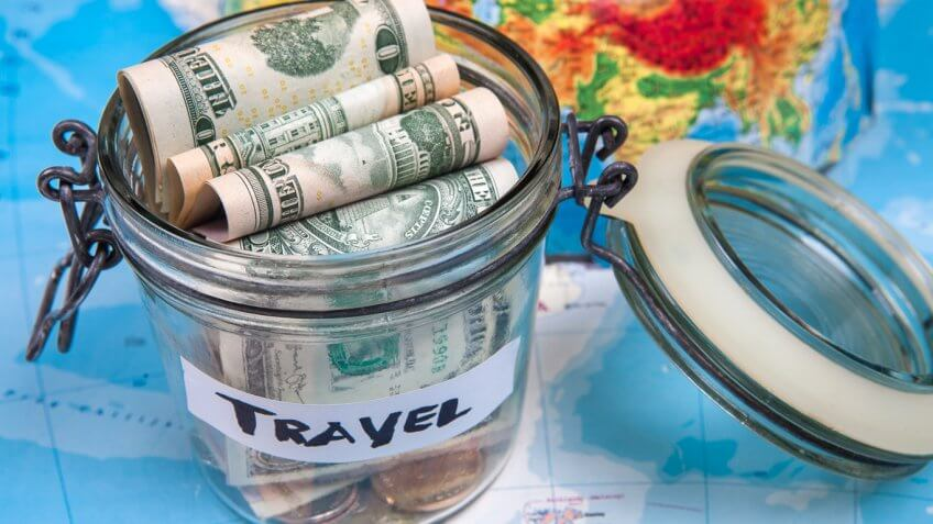 cash bills money in a glass jar labeled travel on top of a world map