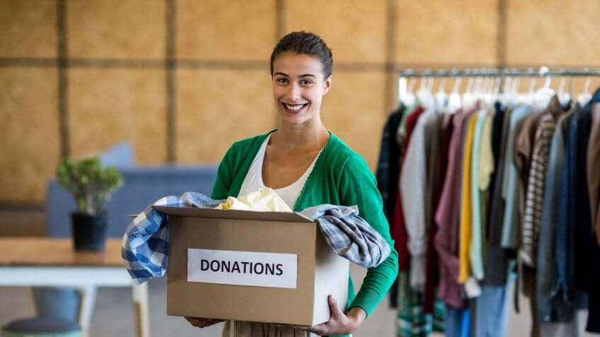 woman holding a box of clothing donations