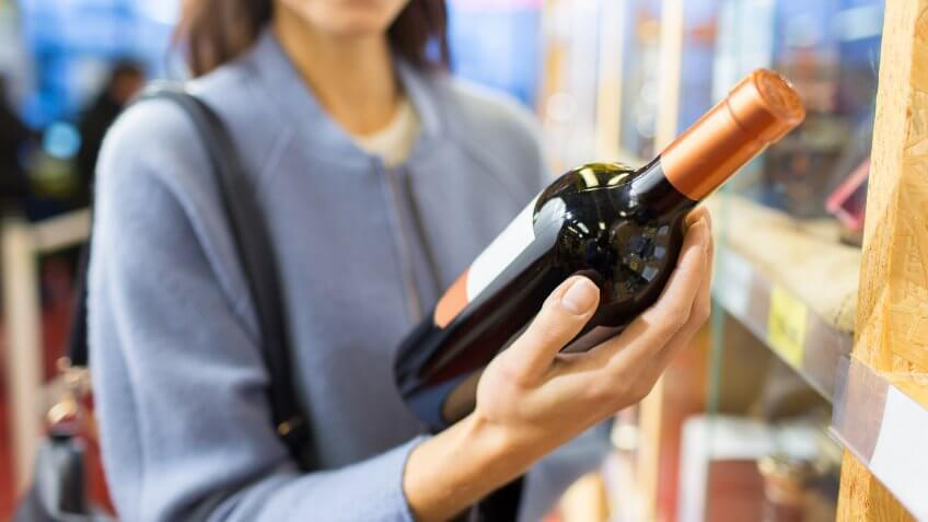 woman buying a bottle of wine