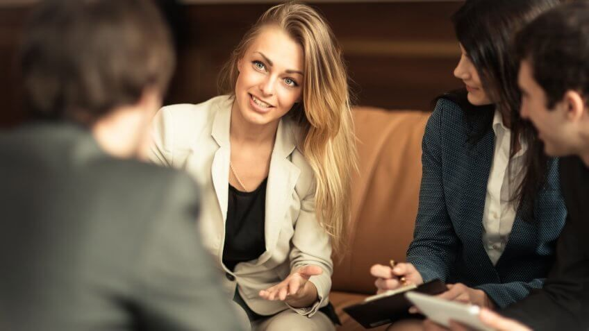 Woman speaking to circle of other coworkers