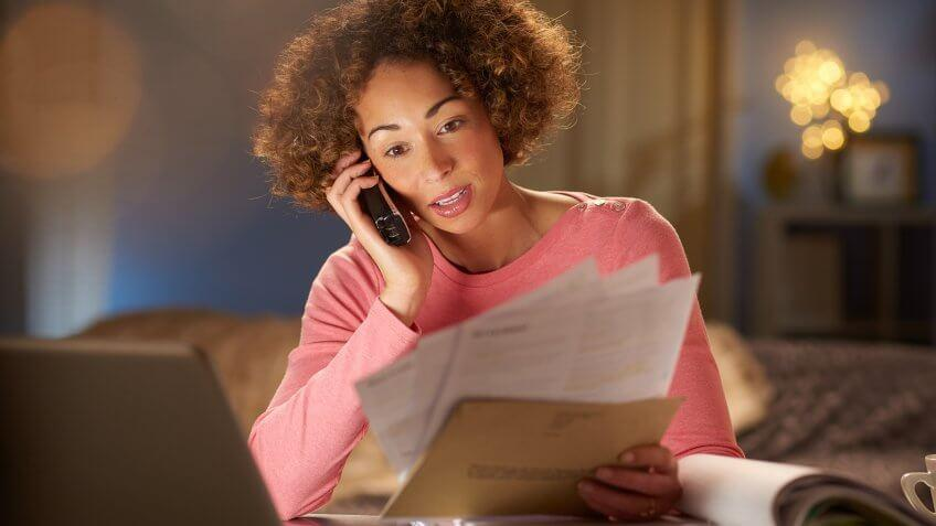 a young woman sits at home , going through her paperwork and bills .