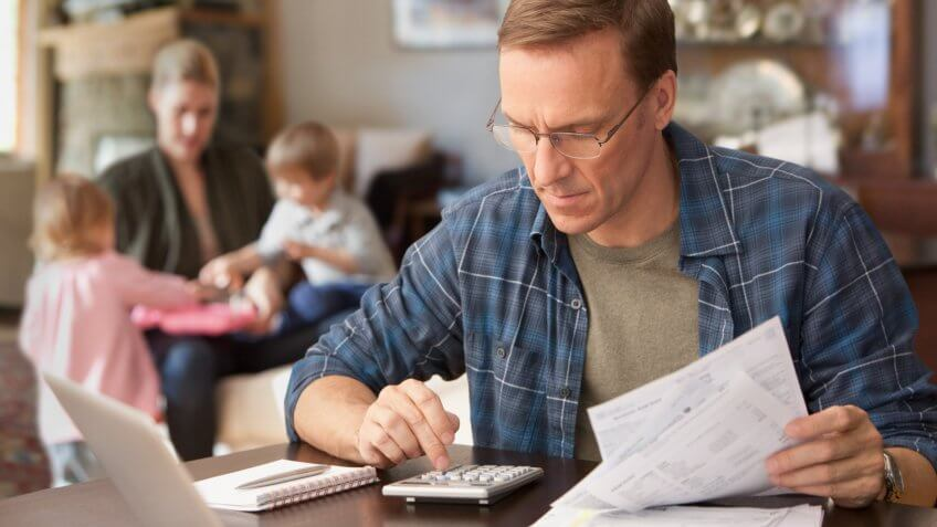 Father paying bills with family behind him.