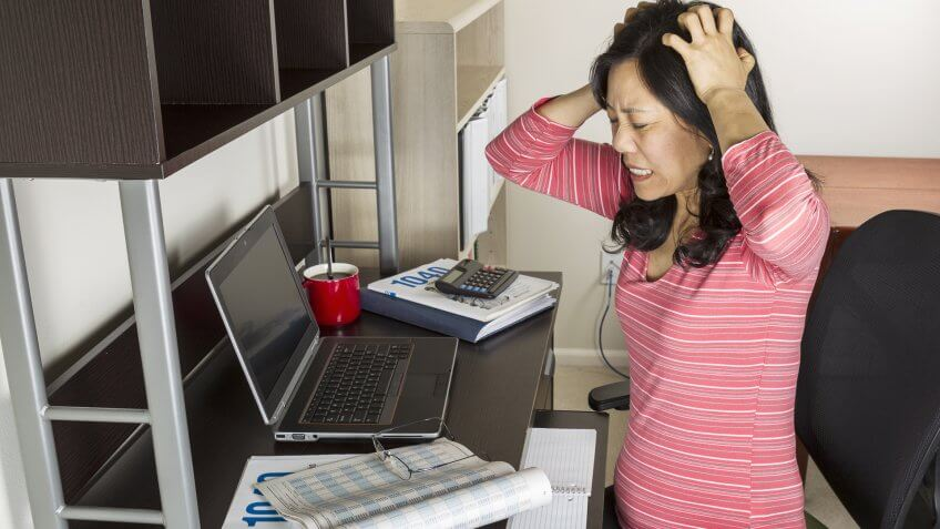 woman looking frustrated at her laptop