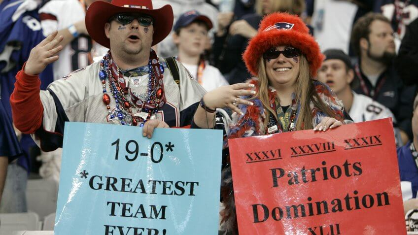 New England Patriots fans hold up signs and four fingers before the Super Bowl XLII football game between the Patriots and the New York Giants at University of Phoenix Stadium, in Glendale, Ariz.