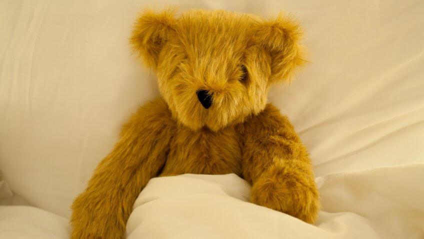 teddy bear tucked in bed