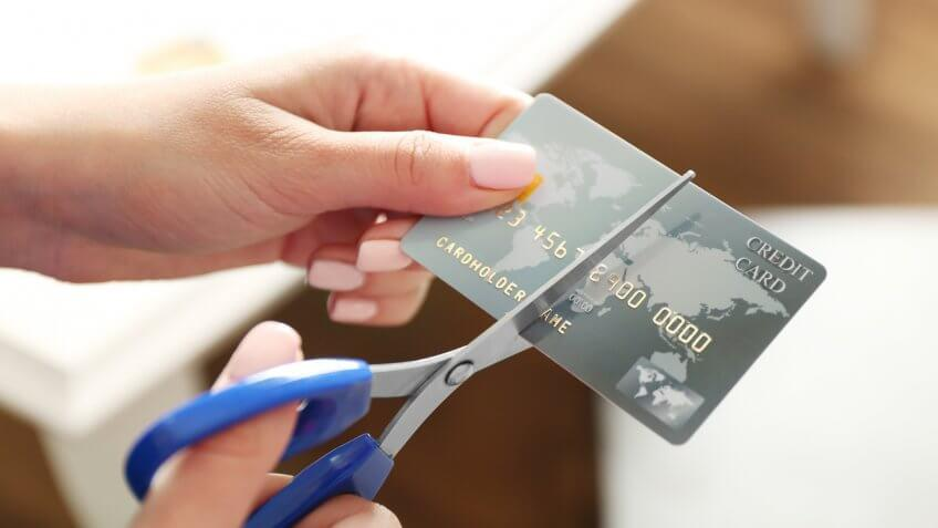 person cutting their credit card