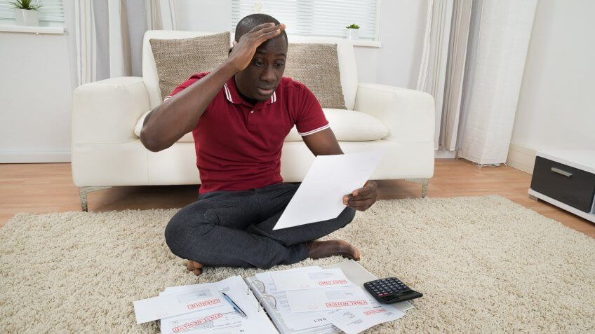 man looking frustrated as he loks at his documents papers