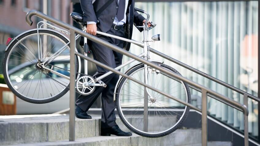 businessman carrying bicycle down the stairs