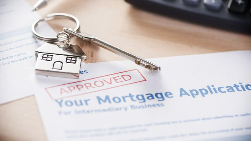 key chain of home and key over an approved mortgage application