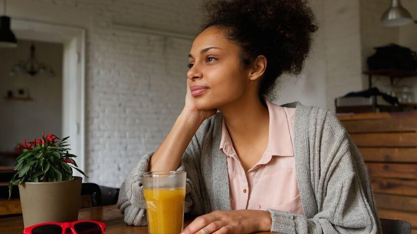 woman drinking orange juice looking out a window