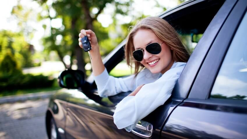 woman smiling in her car dangling car keys