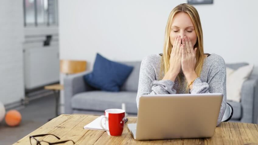 woman looks shocked with her laptop open