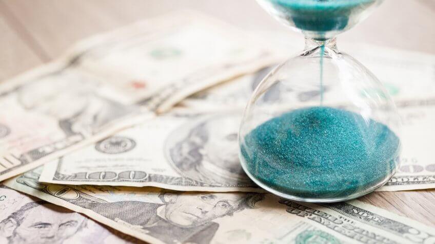 hourglass over money bills cash