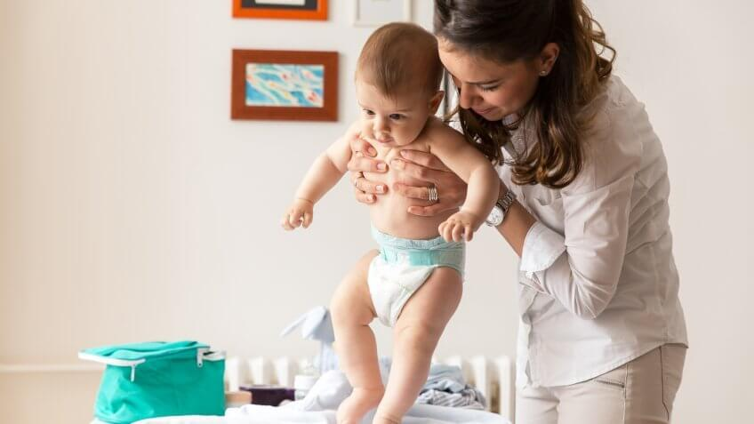 woman holding baby wearing a diaper