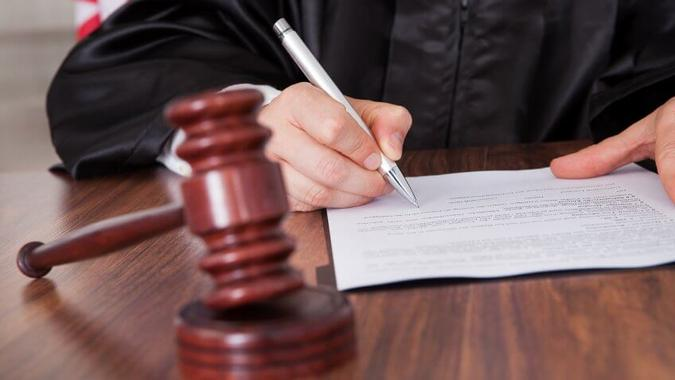 Close-up Of Male Judge  Writing On Paper In Courtroom.