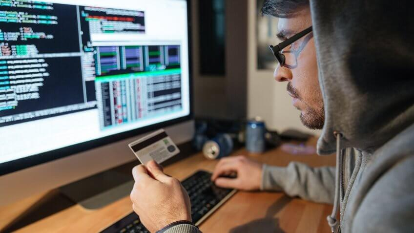 Concentrated young hacker in glasses stealing money from diferent credit cards sitting in dark room.
