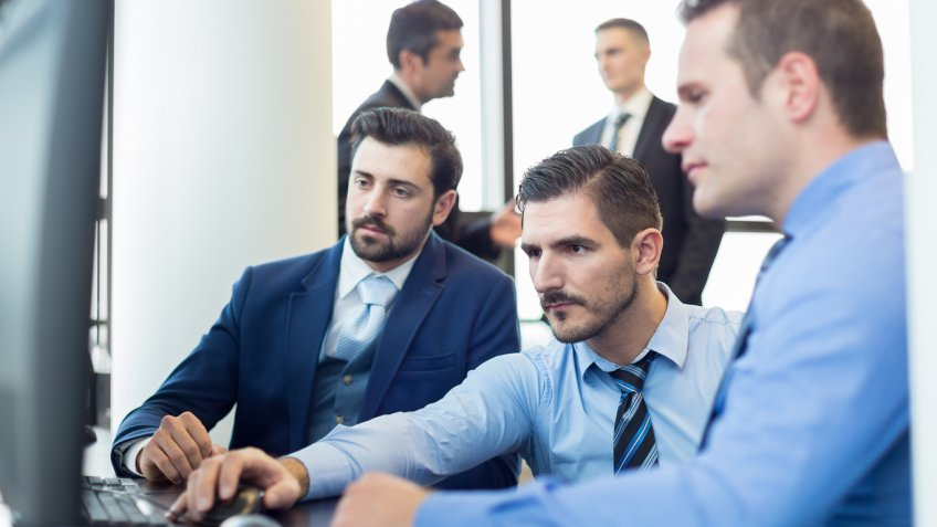 group of men sitting around a computer
