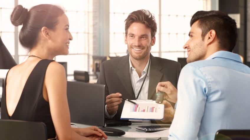 adviser pointing to a chart with a young man and woman looking at each other