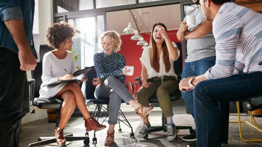 group of coworkers laughing and talking with each other