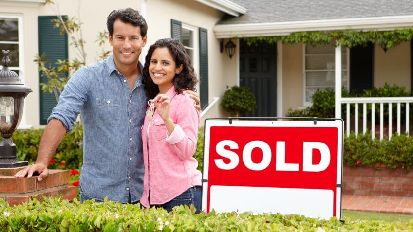 couple standing in front of a sold home