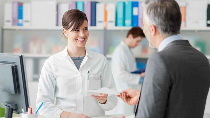 pharmacist handing a script to a man