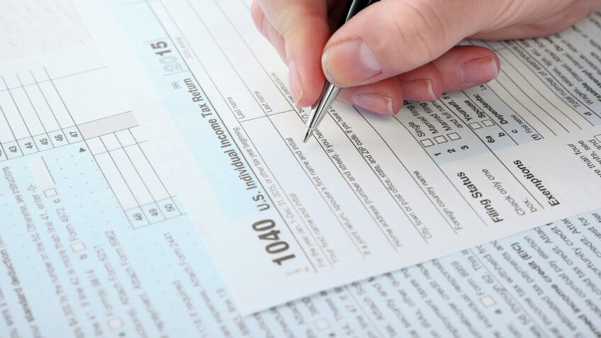 person filling out their 1040 individual income tax return form