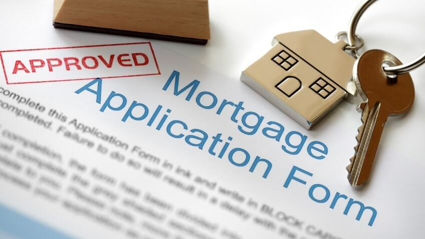 Approved Mortgage loan application with house key and rubber stamp.