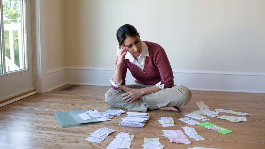 Woman looking at bills and receipts on floor.