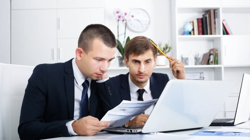 two young confused business men staring at documents and laptop