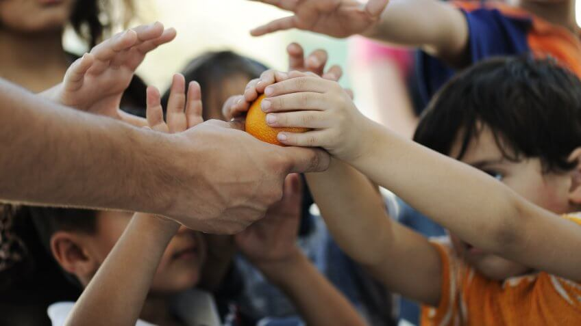 man giving orange to little children