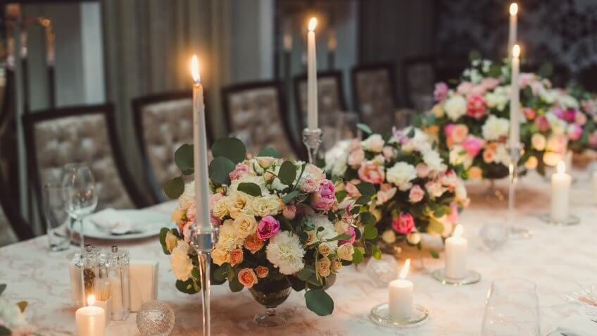 floral arrangements and candles on a wedding dining table
