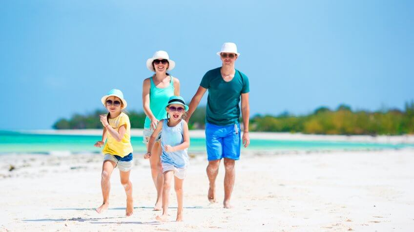 family vacationing playing on the beach
