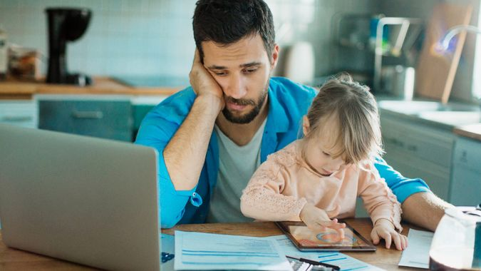 Photo of a father and daughter sitting in kitchen,father is doing home financials while daughter is having fun with digital tablet.