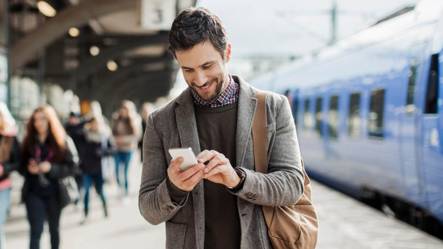 Photo of a smiling businessman texting on his mobile phone at train station.