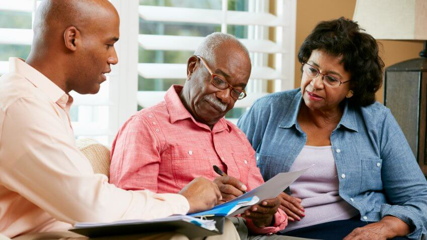 senior older couple filling out paperwork with younger man