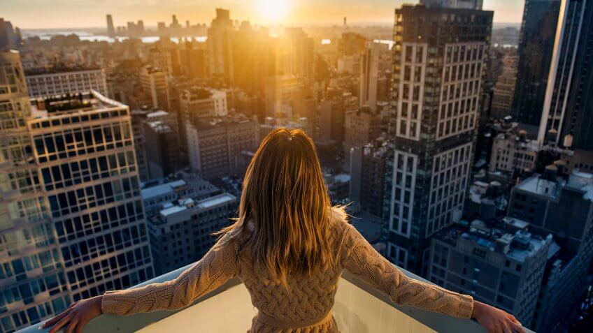 Rich woman enjoying the sunset standing on the balcony at luxury apartments in New York City.