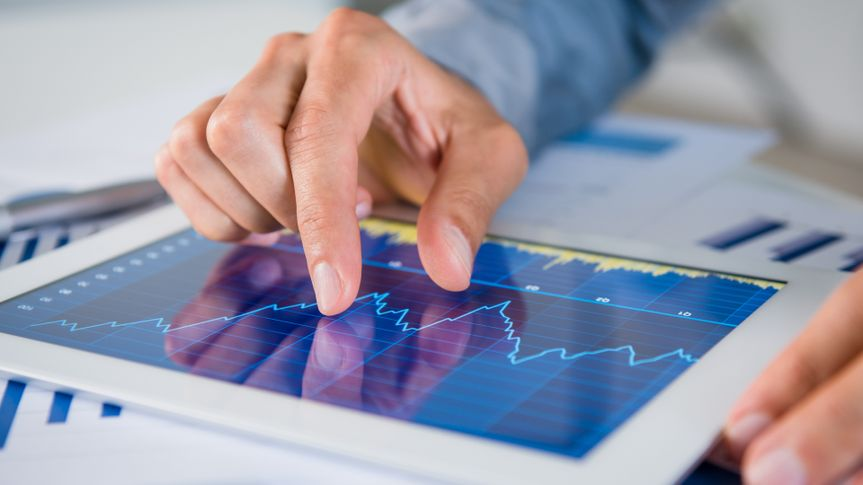 Close Up Of Businessman's Hand Analysing Graph On Digital Tablet.