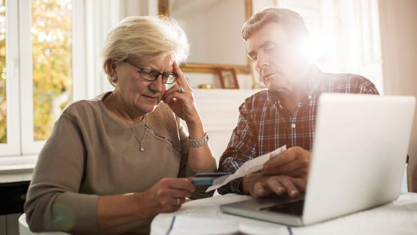 Senior couple sitting at home and having problems with paying their bills.