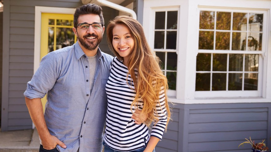 Couple Standing Outside New Home