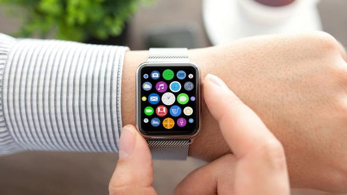 Man hands and smart touch watch with home screen icons apps.