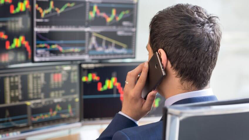 Over the shoulder view of and stock broker trading online while accepting orders by phone.