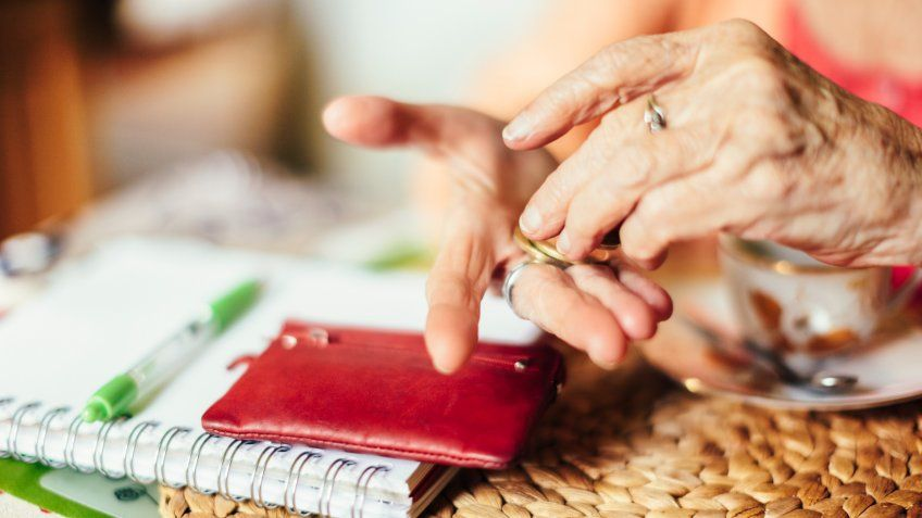 Senior woman calculating finances in her kitchen.