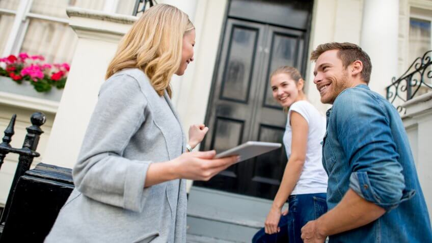 Couple buying a house with a real estate agent.