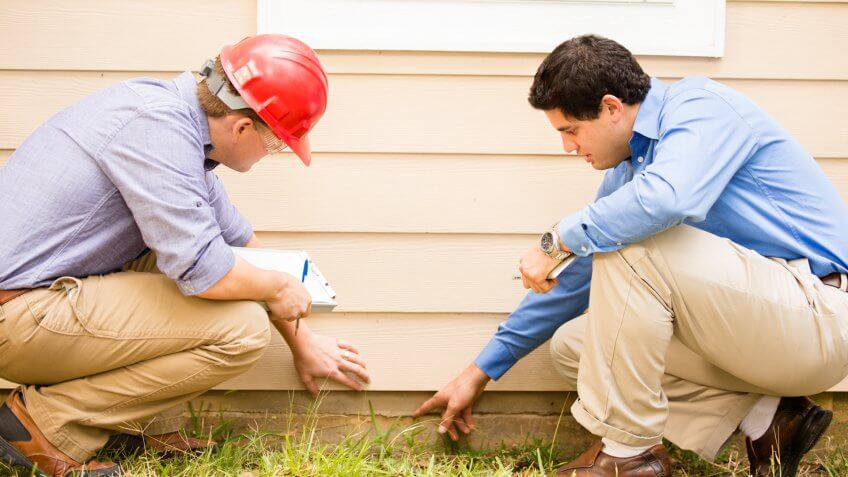 examining a home's exterior wall and foundation