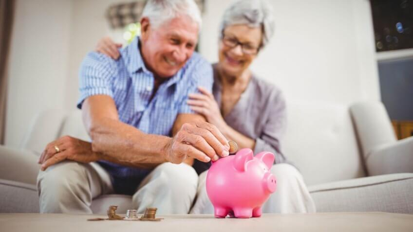 senior old retired couple putting coin into piggy bank