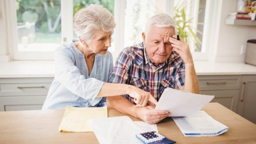 older senior retired couple looking over paper documents